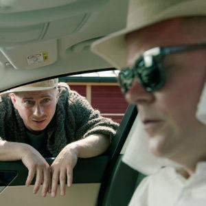 Tommi istuu autossa valkoisiin vaatteisiin suojautuneena, Juhis kurottaa sisään avonaisesta ikkunasta.