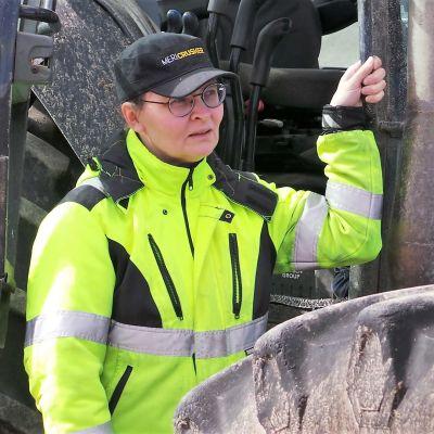 Nainen seisoo traktorin vieressä.