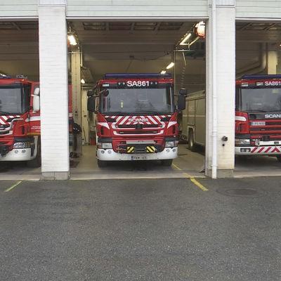 Kolme paloautoa kalustohallissa.