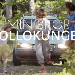 bild på när 3 personer springer under en bil på en sommrig väg.