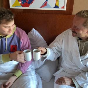 UMK-voittaja Aksel Kankaanranta hotellihuoneen sängyssä aamiaisella kylpytakkiin pukeutuneen Mikko Silvennoisen kanssa.