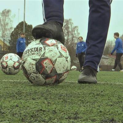 Fötterna på en fotbollsspelare som har ena foten på bollen. I bakgrunden syns fler fotbollsspelare.