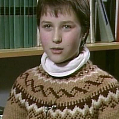 Nuori nainen istuu kirjahyllyn edessä haastateltavana. 80-luku.