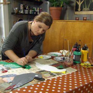 Camilla Forsén-Ström målar papegojor i trä.