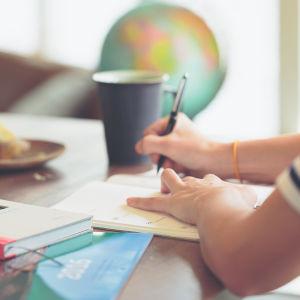 Henkilö opiskelee pöydän ääressä.