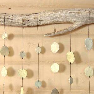 Närbild av konstverk bestående av strandfynd och hängande lerstenar