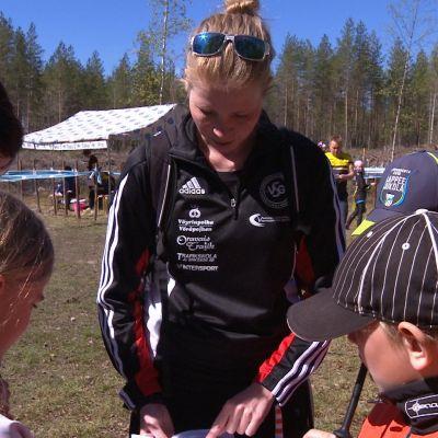 Tränaren Sabina Bäck visar orienteringskarta åt en grupp barn.
