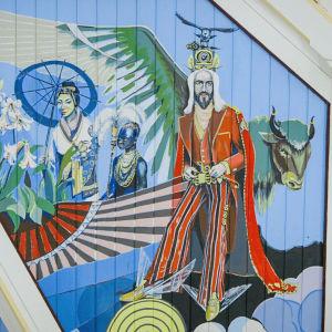 Kirkasvärisiä kattomaalauksia kirkon sisäkatossa, jeesus, eri etnisiä ryhmiä edustavia enkeleitä.