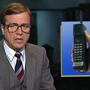 Arvi Lind lukee uutista NMT-puhelimesta.