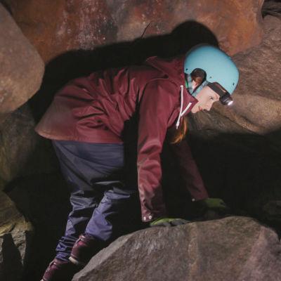 Nainen sinisessä kypärässä ja otsalampussa kävelee kumarassa luolassa.