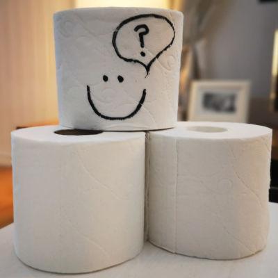 toalettpappersrullar på ett bord - en har en smiley ritad på sig
