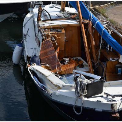 En motorseglare har blivit påkörd av en motorbåt och ligger nu vid en brygga med skador på babords sida och bakre däck.