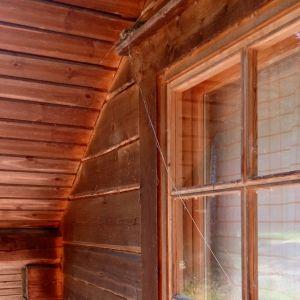 Ett fågelbo ovanför ett fönster, från boet hänger ett långt grässtrå.