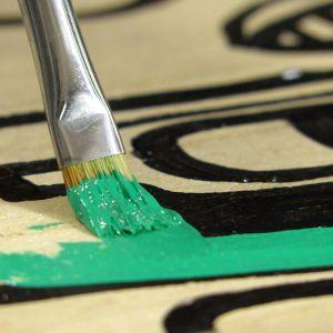 Grön färg målas in ett totemmärke.