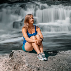 Sini Finsk istuu kivellä Myllykulmankosken äärellä silmät suljettuina ja kuuntelee kosken kohinaa.