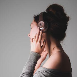 Nainen kuuntelee musiikkia kuulokkeilla.