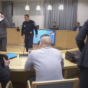 Käräjäoikeuden istuntosalissa syytettyjä ja asianajajia.