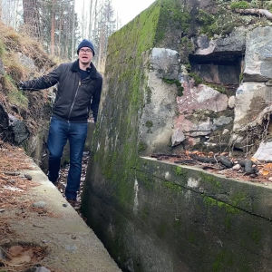 En man som går i en gång inne i en befästning bestående av höga murar.