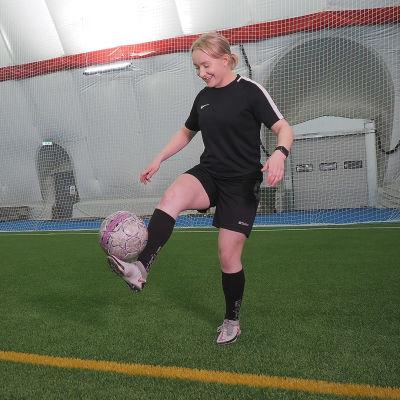 Bettina Peltoniemi tasapainoilee jalallaan jalkapalloa.