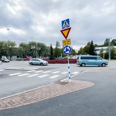 Kiertoliittymä jossa menee autoja. Kiertoliittymän liikennemerkki etualalla.