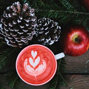 Punaiset omenat, iso käpy ja jouluinen kahvikuppi.
