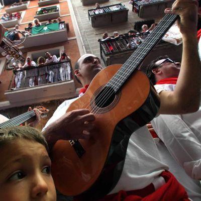 Perinteisiin asuihin pukeutuneet miehet soittavat kitaraa Pamplonan härkäjuhlilla.