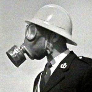 Poliisiupseeri kaasunaamarissa ja kypärässä Lahden messujen väestönsuojelunäytöksessä 1969.
