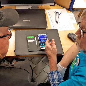 Mies opastaa toista tietotekniikassa Kajaanin kirjastolla Nettiä ikä kaikki -tapahtumassa. Pöydällä kännykkä auki.