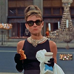 Audrey Hepburn syö aamiaistaan kultasepänliike Tiffanyn näyteikkunan ääressä elokuvassa Aamiainen Tiffanylla