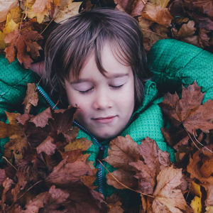 Anonyymi poika makaa silmät kiinni lehtikasassa.