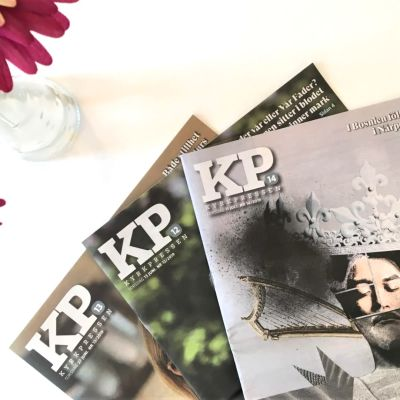 Tre nummer av Kyrkpressen ligger på ett bord brevid en vas med blommor.