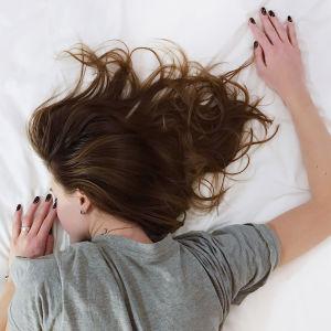 Nainen makaa vatsallaan sängyllä.