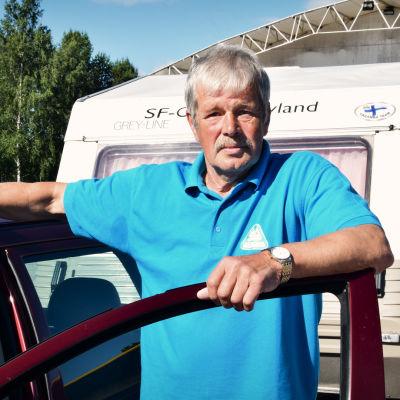 Olof Bussman i klädd en turkos pikéskjorta står lutad mot en bildörr. I bakgrunden skymtar en husvagn.