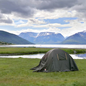 Ett tält som står uppspänt på ett norskt gräsfält i ett fjordlandskap.