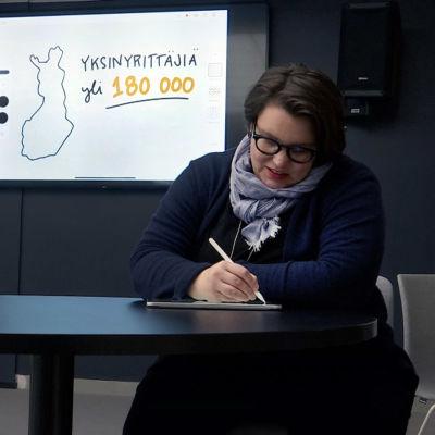 Nainen kuvittaa livenä seminaaria.