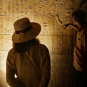 Ihmiset tutkivat hieroglyjejä luolassa.