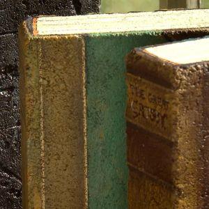 Närbild på målade tegelstenar föreställande gamla böcker.
