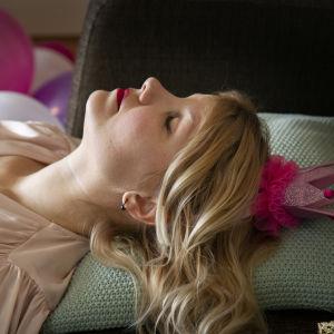 Sari Casal makaa väsyneenä leikkikruunu päässä.