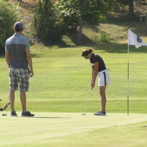 Tre personer står på greenen på en golfbana och gör sig redo att putta.