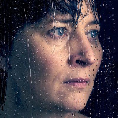 Lähikuvassa Wanda Dubiel, joka näyttelee Puhdistus-monologissa Aliide Truuta. Hänet on kuvattu vesipisaroita valuvan ikkunan läpi.