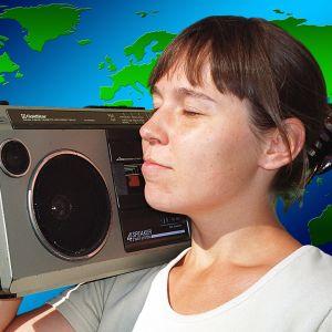 Tyttö matkaradion kanssa, taustalla maailmankartta.