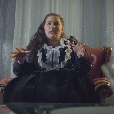 Nainen istuu nojatuolissa.