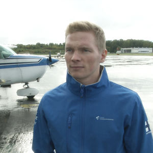 Gymnasten Tomi Tuuha står bredvid ett flygplan