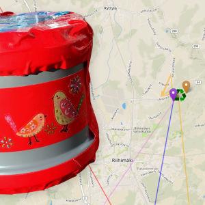 En röd plastbehållare framför en karta över återvinningscentralen i Riihimäki