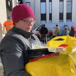 Laura Pyykkönen kantaa käsissään isoa keltaista muovipussia täynnä ruokaa.