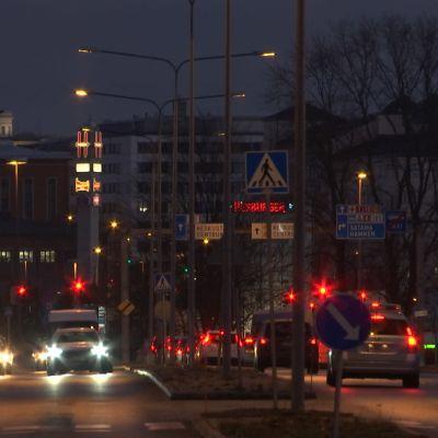 Gata i Åbo i mörker, många bilar köar vi trafikljus.