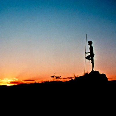 Nuori mies lannevaatteessa seisoo profiilissa aavikolla vasten auringonlaskua. Kuva elokuvasta Walkabout.