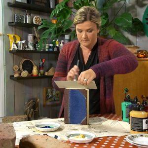 Camilla Forsén-Ström målar en tegelsten som en bok.