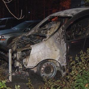 En utbränd bil på en parkeringsplats.