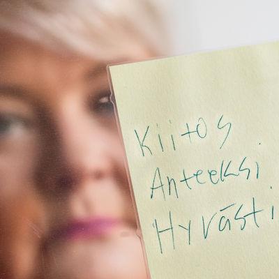 Sari Palmunen pitää käsissään Mikko-pojan jäähyväisviestiä.